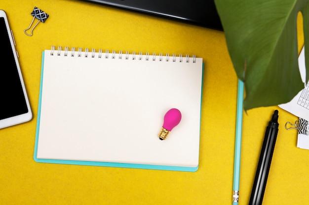 Cuaderno con lugar para texto y lápiz sobre un escritorio amarillo de un empresario