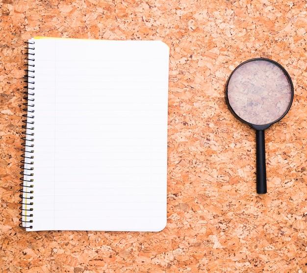 Cuaderno y lupa sobre escritorio.