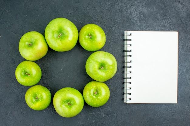 Cuaderno de manzanas verdes de fila de círculo de vista superior en mesa oscura