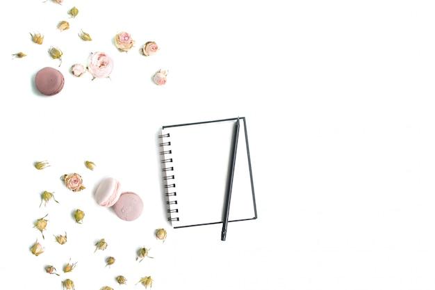 Cuaderno maqueta, lápiz y rosas frescas sobre fondo blanco de madera. vista superior, endecha plana.
