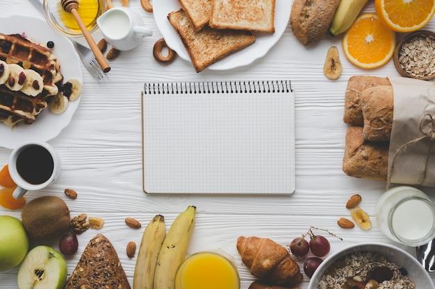 Cuaderno en medio de pasteles y frutas