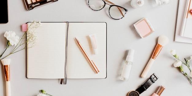Cuaderno metálico dorado rosa con productos de belleza