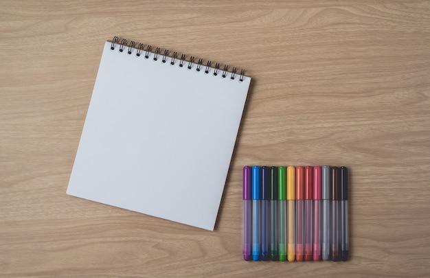 Cuaderno con muchos bolígrafos coloridos en mesa de madera marrón