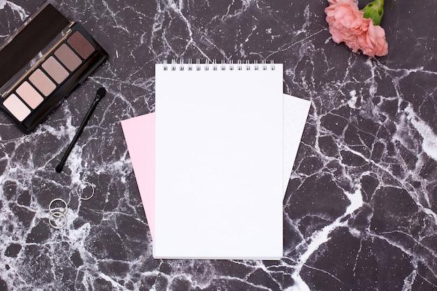 Cuaderno de mujer y cosméticos en mesa de mármol negro.