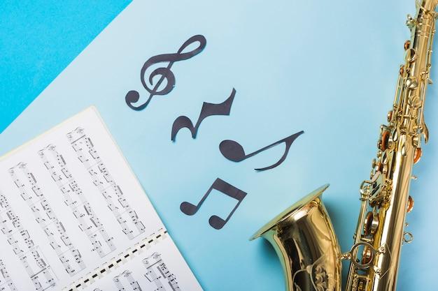 Cuaderno musical y saxofones dorados sobre fondo azul.