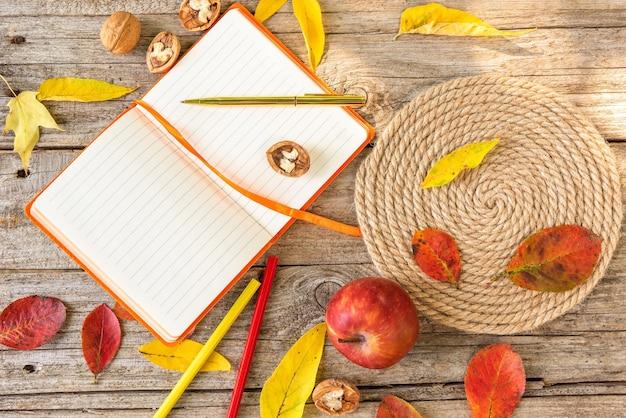 Cuaderno naranja entre hojas de otoño.