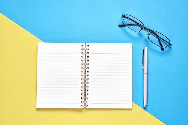 Cuaderno negro de la pantalla en blanco y pluma colocada en fondo amarillo y azul en colores pastel.