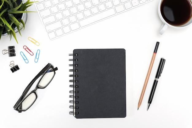 Cuaderno negro sobre fondo de mesa de escritorio blanco con espacio de copia