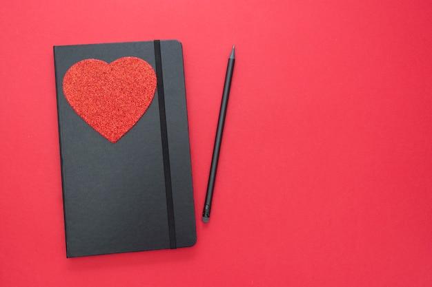 Cuaderno negro sobre fondo rojo con un corazón. mesa para un amor, mensaje de san valentín.