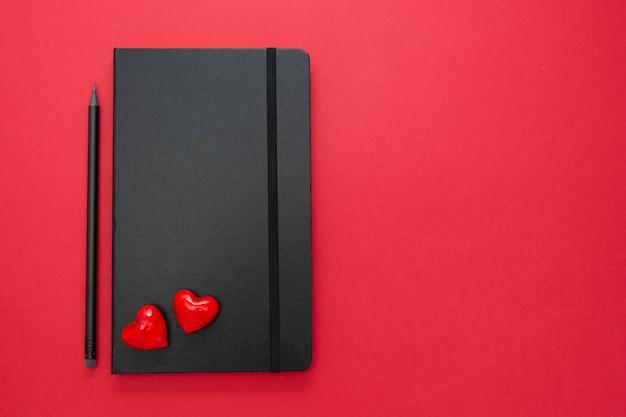 Cuaderno negro sobre fondo rojo con dos corazones. mesa para un amor, mensaje de san valentín.