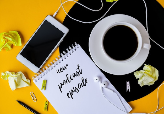 Cuaderno con new podcast episode disponible ahora con letras. auriculares y teléfono móvil. diseño de vista superior. lugar de trabajo. audiolibros