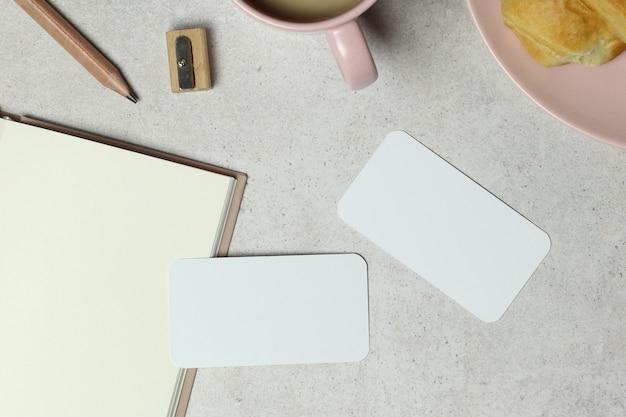 Cuaderno de notas, tarjetas, lápiz de madera y sacapuntas sobre granito.