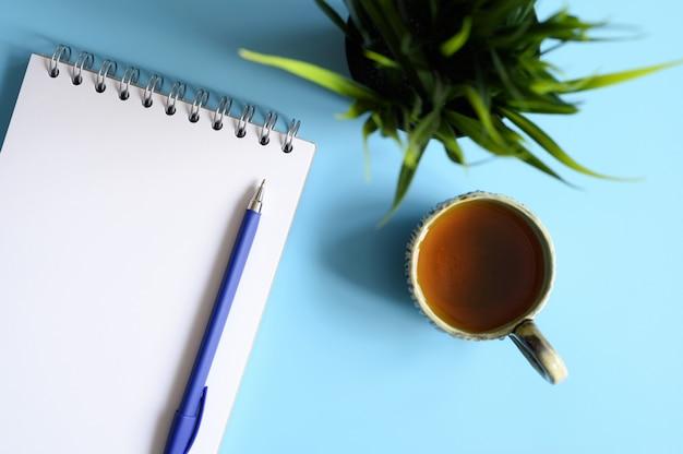 Cuaderno o cuaderno de dibujo y un bolígrafo y una taza de té y planta verde sobre un fondo azul.