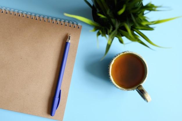 Cuaderno o cuaderno de dibujo hecho de papel artesanal y un bolígrafo y una taza de té y una planta verde