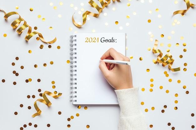 Cuaderno de objetivos de año nuevo 2021 con decoraciones festivas sobre una mesa blanca. endecha plana