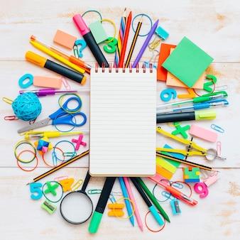 Cuaderno con objetos de la escuela en el fondo de madera.
