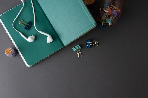 Cuaderno de página verde abierto con auriculares y clips de papel. maqueta minimalista