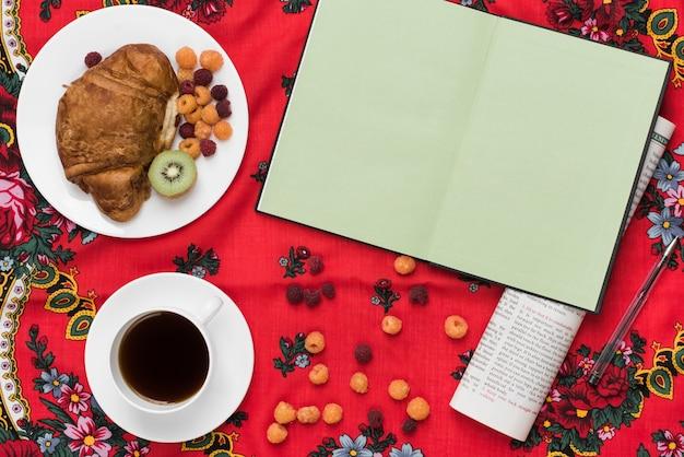 Cuaderno de página verde en blanco; periódico; desayuno; bolígrafo; café sobre mantel rojo