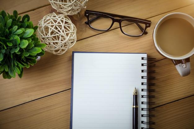 Cuaderno con páginas en blanco en mesa de madera.