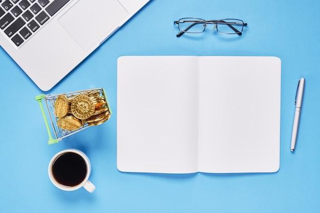 Cuaderno de pantalla negro en blanco y portátil colocado fondo azul.