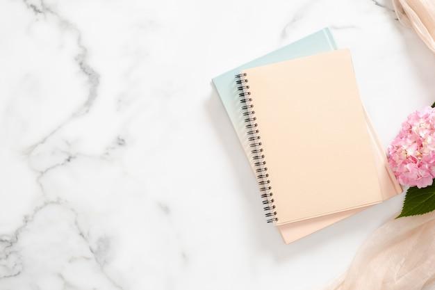 Cuaderno de papel en blanco, flor de hortensia rosa, fondo de manta pastel