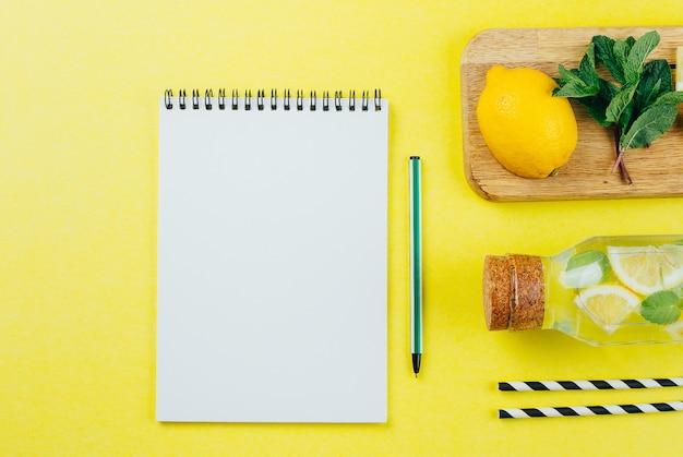 Cuaderno de papel blanco y limonada con ingredientes.