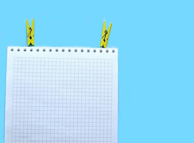 Cuaderno de papel blanco sobre un fondo azul y dos pinzas amarillas.