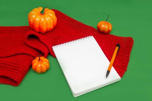 Un cuaderno de papel, un bolígrafo, calabazas naranjas y una bufanda de punto cálida roja sobre un fondo verde. vista superior. copie el espacio. bloc de notas para anotar listas de otoño