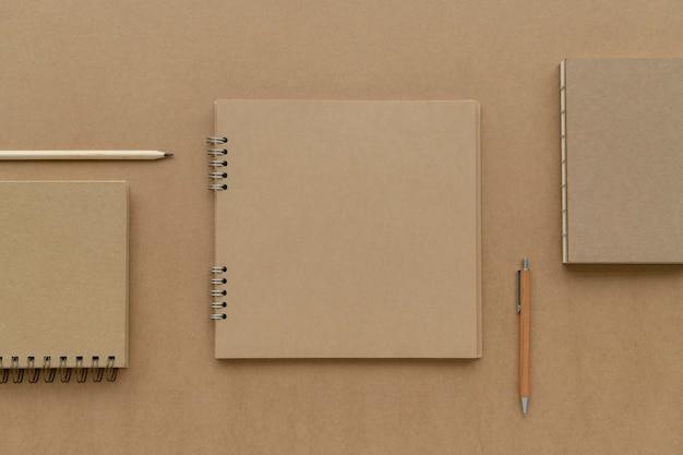 Cuaderno de papel marrón natural con maqueta de lápices