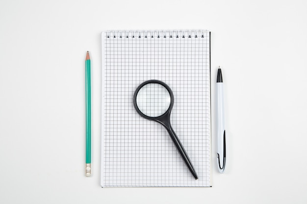 Cuaderno de papel con pluma o lápiz sobre fondo blanco aislado. vista superior. aplanada bosquejo