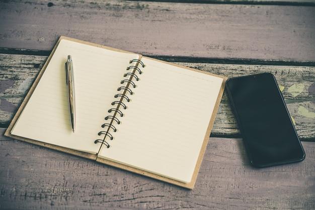 Un cuaderno de papel con una pluma y un teléfono inteligente en la mesa de madera