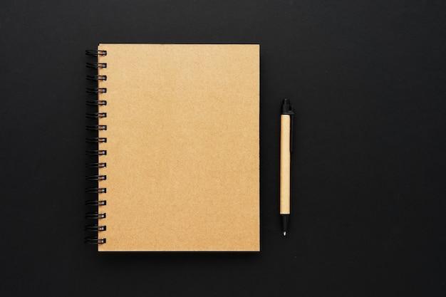 Cuaderno de papel reciclado cerrado y bolígrafo sobre fondo negro.