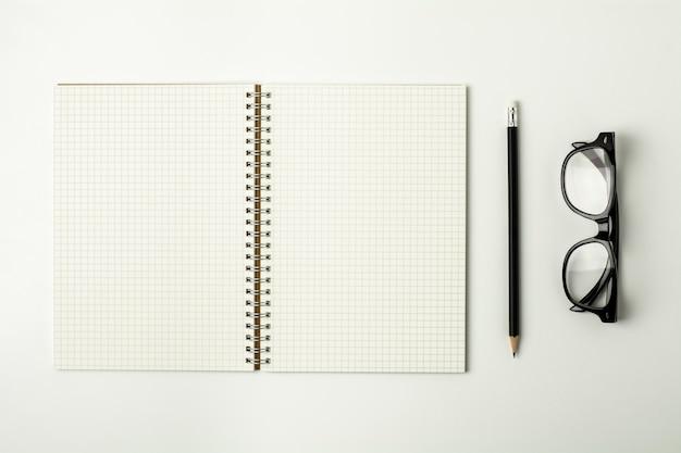Cuaderno de papel de la rejilla, lápiz y gafas en el escritorio blanco - para el fondo del concepto del negocio