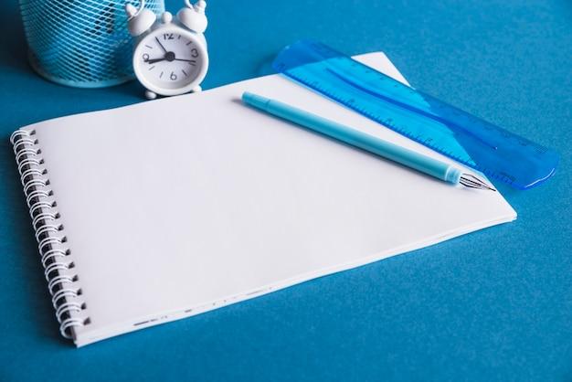 Cuaderno de papel vacío con bolígrafo y reloj