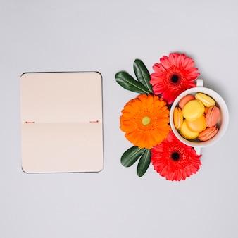 Cuaderno con pequeñas galletas y flores en la mesa