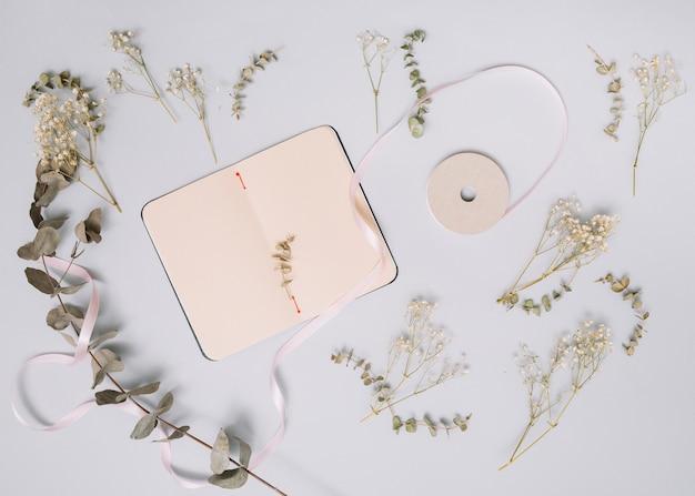 Cuaderno con pequeñas ramas en mesa