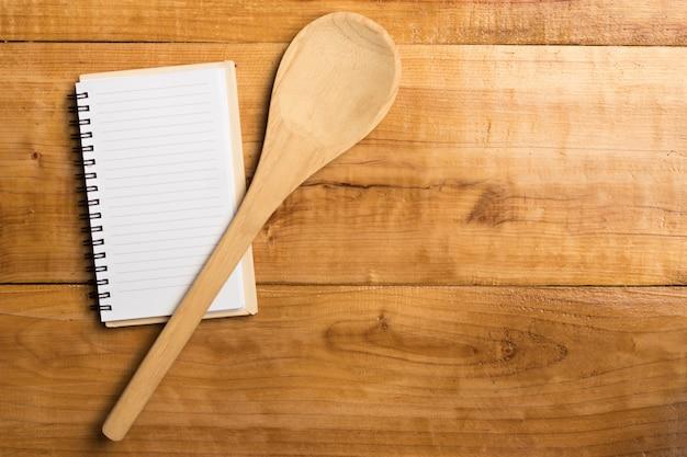 Cuaderno pequeño y cuchara de madera sobre mesa de madera.