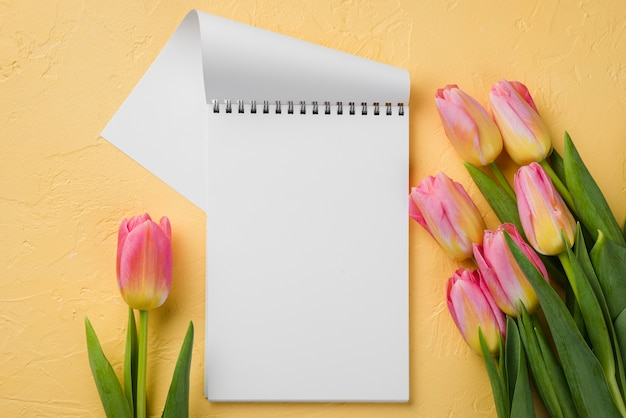 Cuaderno plano al lado de tulipanes