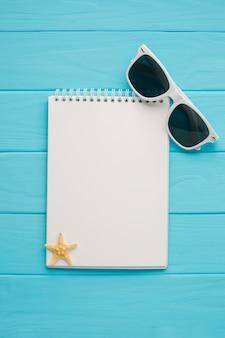 Cuaderno plano laico con gafas de sol.