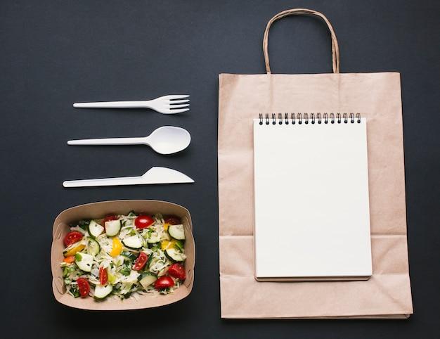 Cuaderno plano sobre maqueta de bolsa de papel