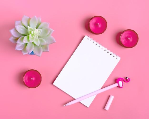 Cuaderno, planta y velas.