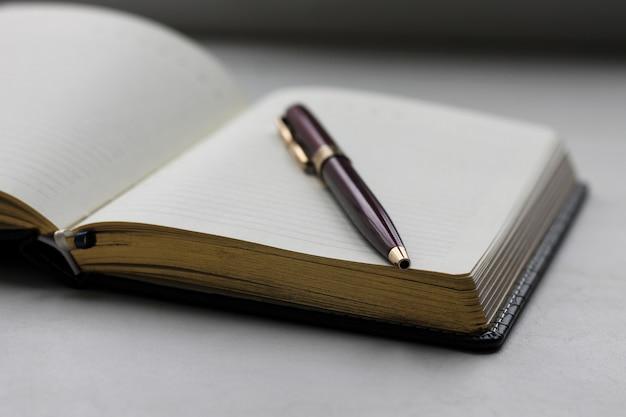 Cuaderno y pluma de cerca. concepto de oficina