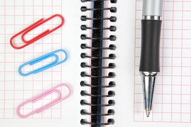 Cuaderno, pluma y clips de papel de cerca.