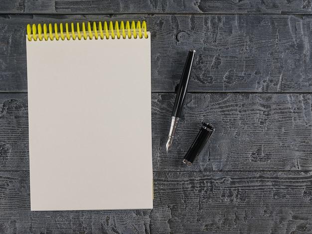 Cuaderno y pluma estilográfica en una vista superior de la mesa oscura. lugar para su texto.