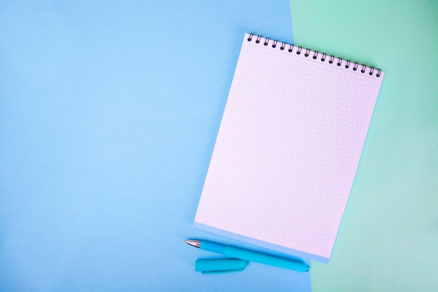 Cuaderno, pluma en fondo azul.