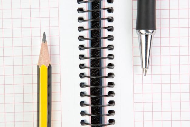 Cuaderno con pluma y lápiz, primer plano.