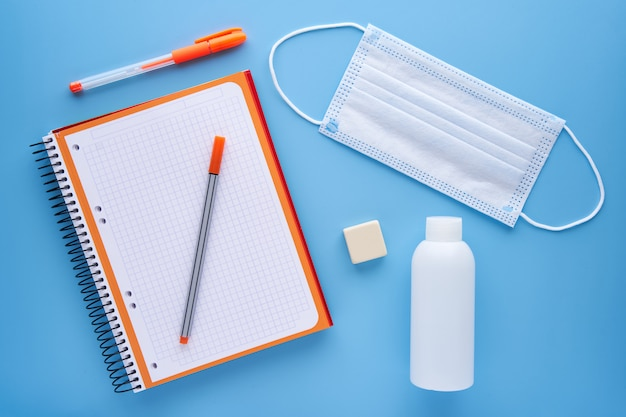 Cuaderno y pluma con una máscara sobre un fondo azul. concepto de regreso a la escuela y protección contra covid.