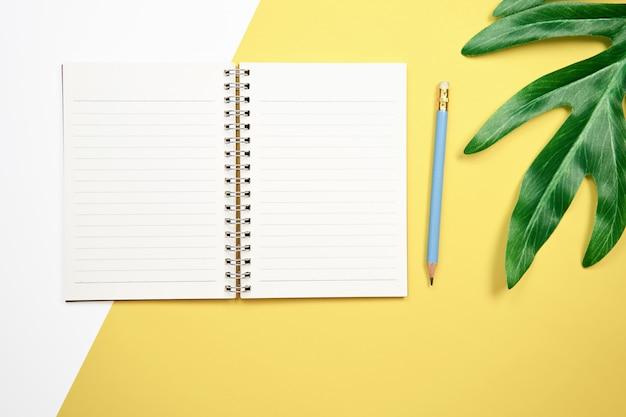 Cuaderno y pluma de la pantalla en blanco colocados en fondo amarillo en colores pastel.