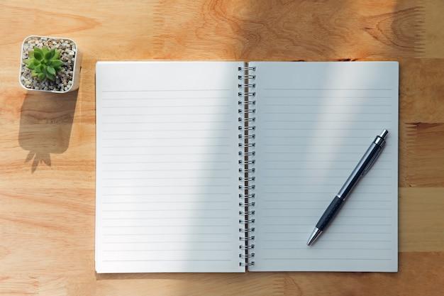 Cuaderno, pluma, planta verde sobre fondo de madera.