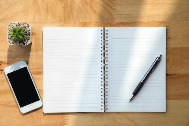 Cuaderno, pluma, planta verde y teléfono inteligente sobre fondo de madera.